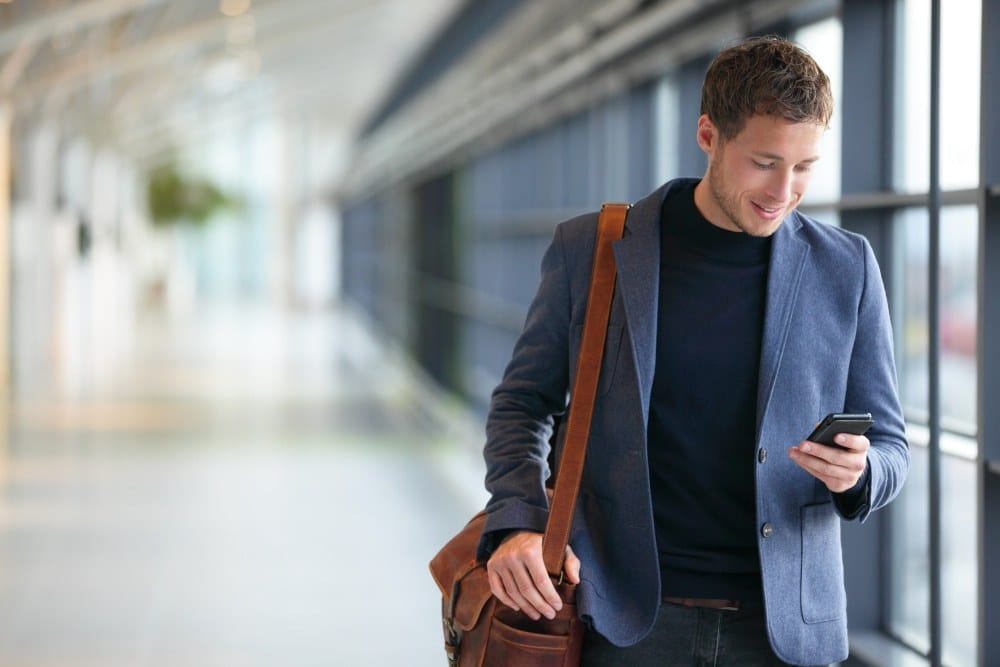Man on smart phone - young business man in airport   How To Document + Optimize Your Processes   Process Optimization   process documentation