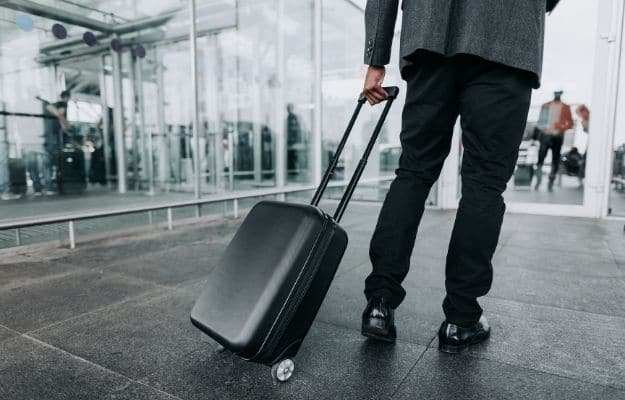Close up of male in business suit is taking suitcase | What to Pack for a Bookkeeping Work Trip | Carry On Suitcase