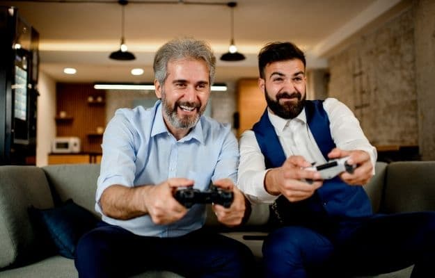 two men are happily playing video game - ca | 9 Skill Building Games for Bookkeepers and Number-Crunchers | Video Games